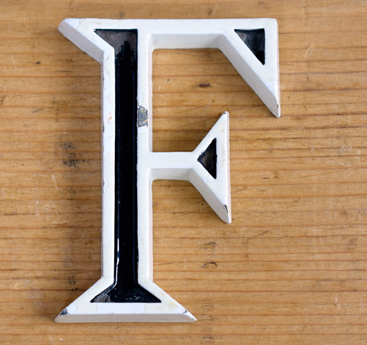 Mid-1900s small vintage monochrome metal sign letter 'F'