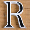 Small black and white metal letter 'R'