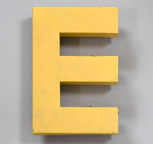 Vintage yellow painted metal shop sign letter 'E'