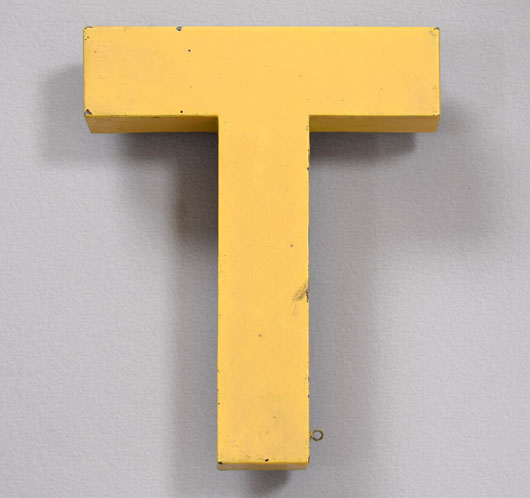 Vintage yellow painted metal shop sign letter 'T'