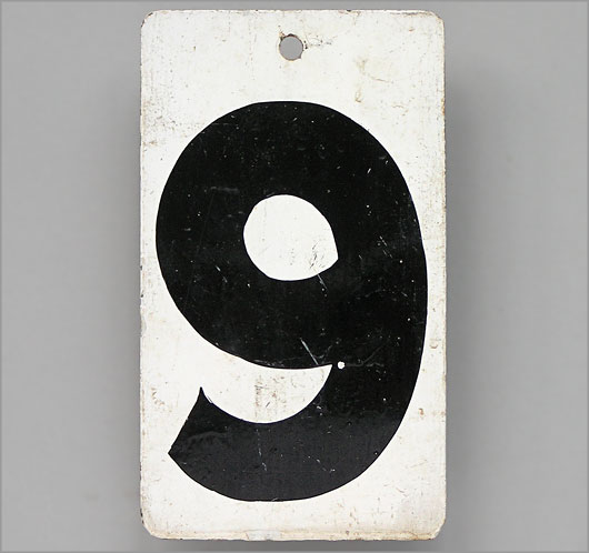 Black and white monochrome vintage metal score marker: '9'