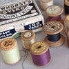 Early-1900s sewing thread box with spools of cotton