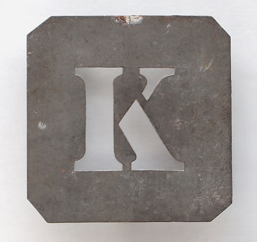 Early-1900s vintage French zinc metal letter stencil: 'K'